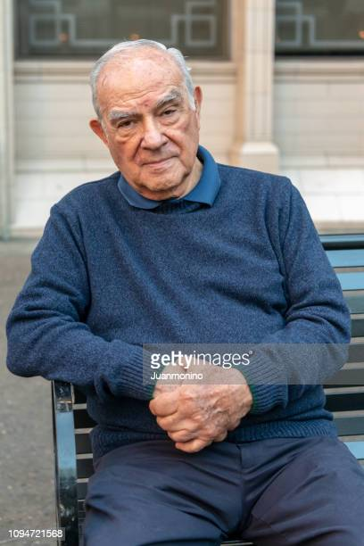 old man sitting in a city bench - minority groups stock pictures, royalty-free photos & images