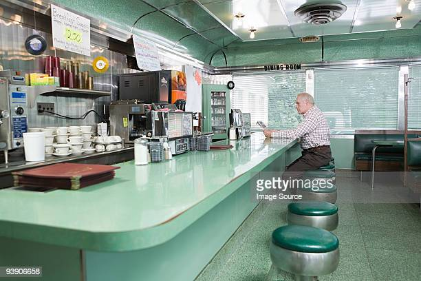old man sitting in a diner - diner stock pictures, royalty-free photos & images