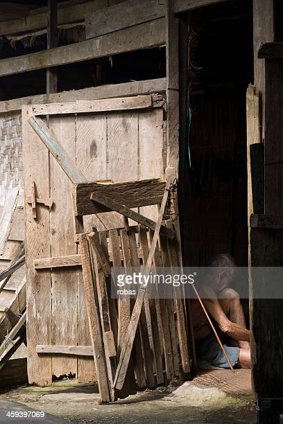 Old man sitting in the door opening of Iban Longhouse
