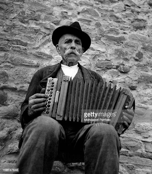 Old man sitting on a low wall and playing accordion 1950s