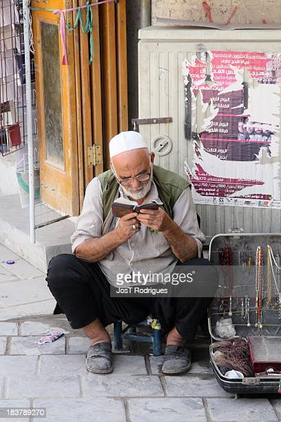 CONTENT] Old man sitting on the sidewalk reading the Koran near the Citadel in Aleppo Syria