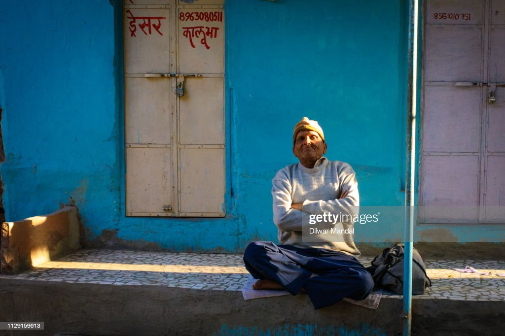 Old man sitting outside of door : Stock Photo