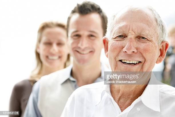 Old man smiling with his son and daughter in background