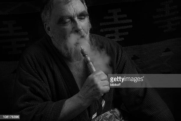 old man smoking hookah from pipe, black and white - hookah stock photos and pictures