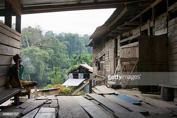 Old man smoking in the porch of a Iban Longhouse