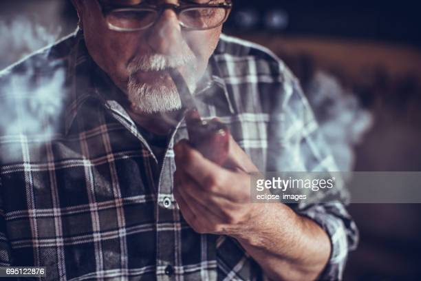 old man smoking with pipe - pipe smoking pipe stock photos and pictures
