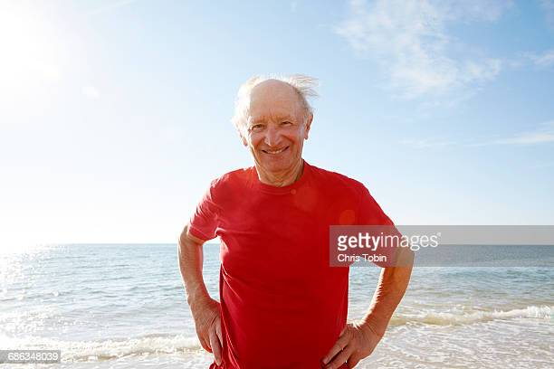 Old man standing near water at the beach