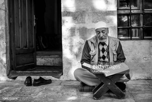 Old man studying in front of the mosque