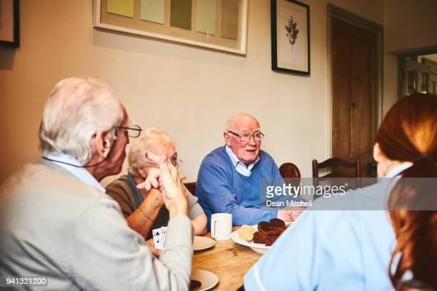 Old man talking with friends at care home