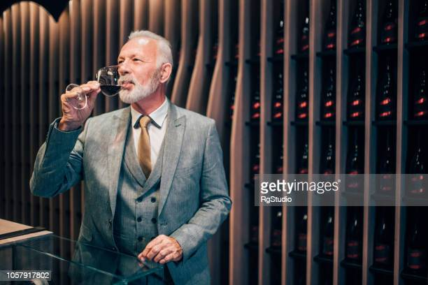 old man tasting red wine - high society stock pictures, royalty-free photos & images