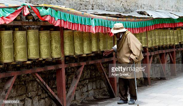 Old man turning budhist prayer wheels in Lhasa, Tibet. These prayer wheels are located behind the Potala Palace.