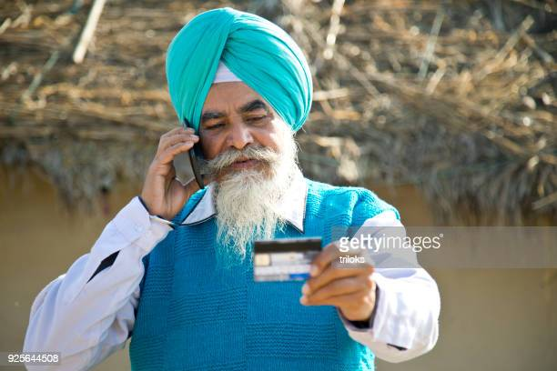 Old man using credit card and mobile phone