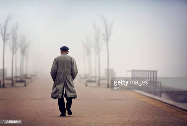 old man walking down empty foggy road - solitude stock pictures, royalty-free photos & images