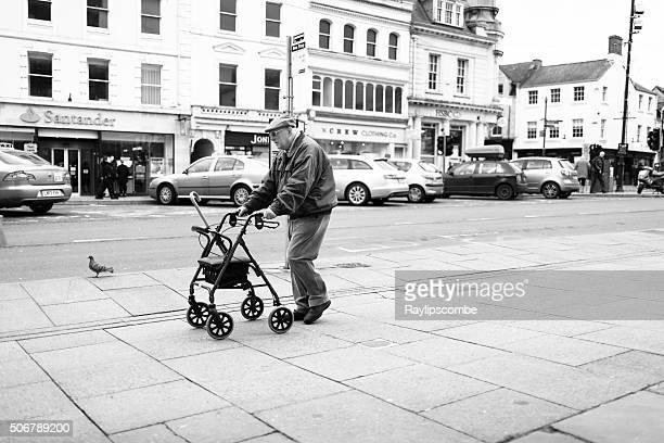 Old man walking through a town centre