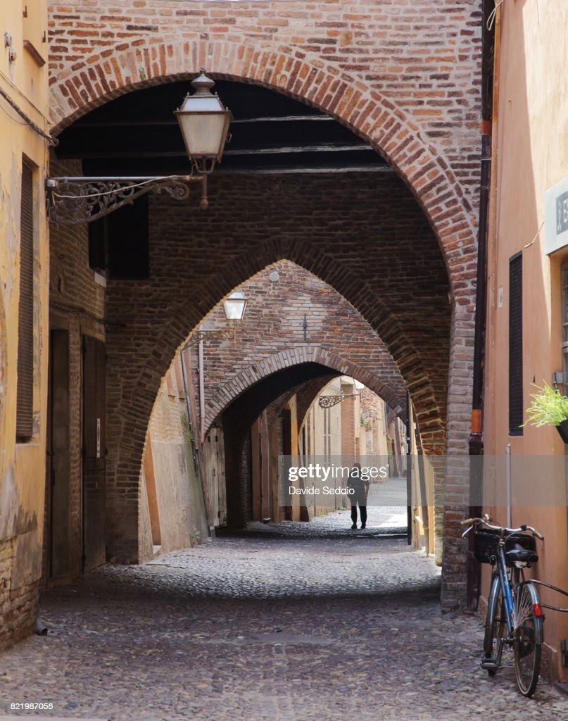 Old man walking under the arches of Ferrara old town : Stock Photo