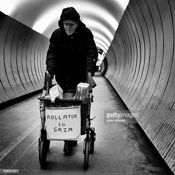 CONTENT] Old man walking with rollator in cylinder shaped tunnel Rollator has the text rollator to gaza written on it