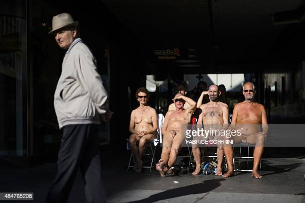 A old man walks past a group performing during the 'Body and Freedom Festival' which bills itself as the world's first ever festival for naked...