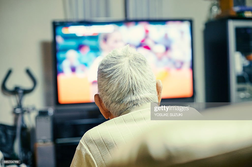 Old man watching TV : Stock Photo