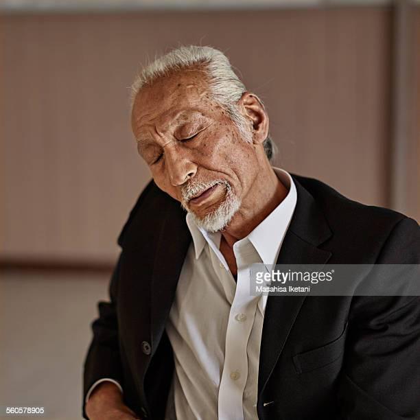 old man wearing a black suit - 首をかしげる ストックフォトと画像