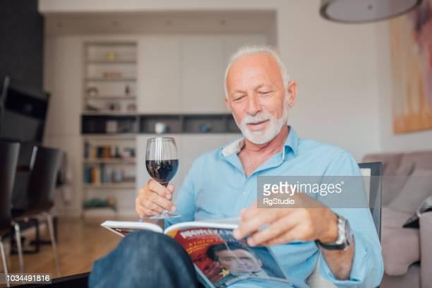 alter mann mit einem glas wein, ein buch zu lesen - einzelner senior stock-fotos und bilder