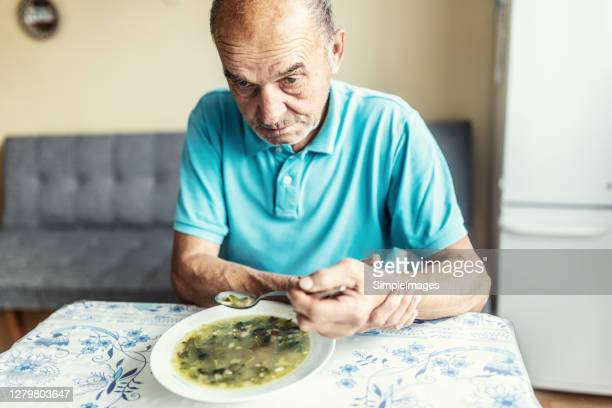 old man with a parkinson disease holds his arm with a hand, trying to eat a soup. - epilepsy stock pictures, royalty-free photos & images