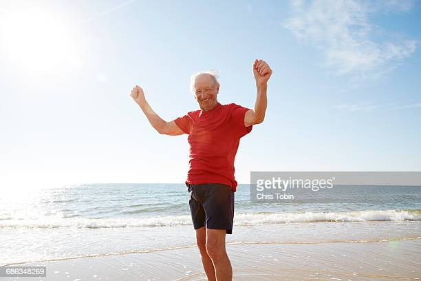 Old man with arms raised at the beach