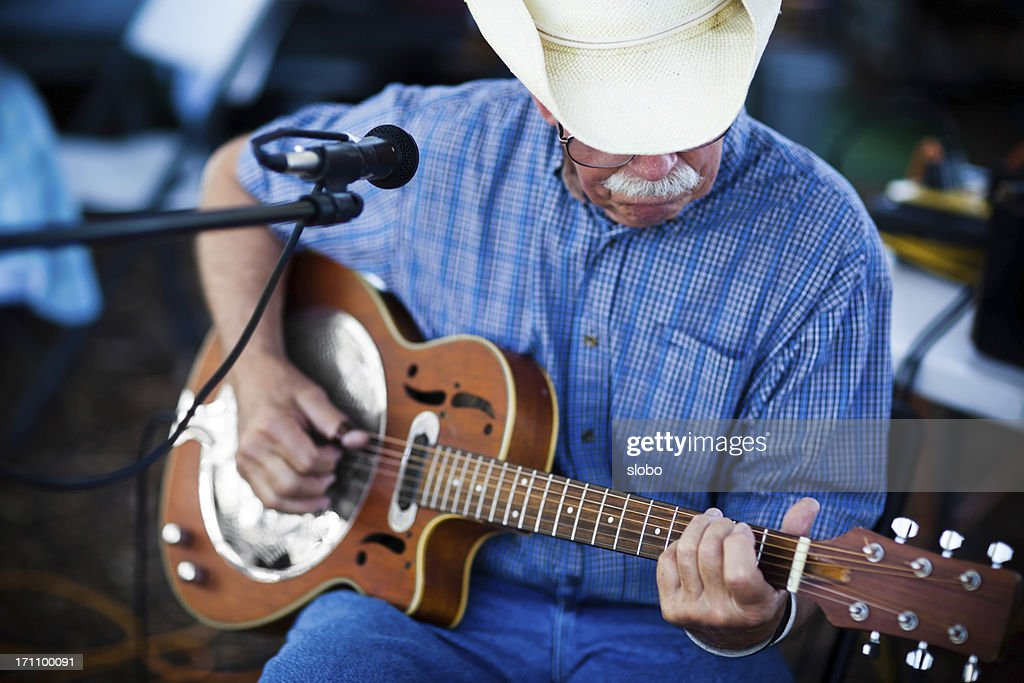 old man with cowboy hat playing blues on a guitar outdoors : Stock Photo