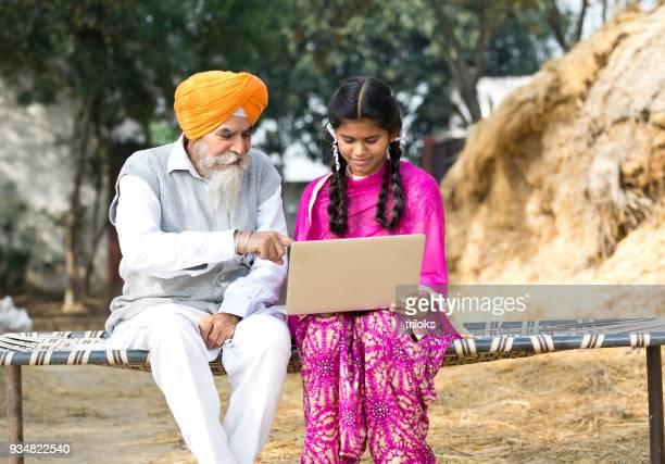 old man with girl using laptop - punjab india foto e immagini stock