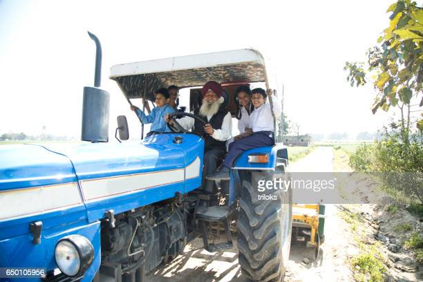 old man with grand children riding tractor - punjab india stock pictures, royalty-free photos & images