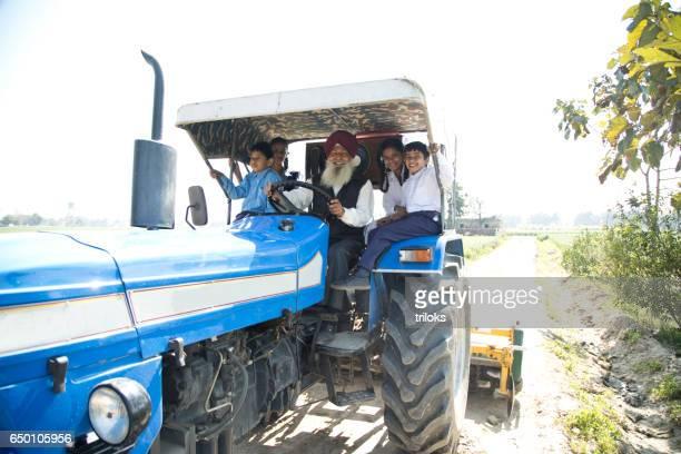 old man with grand children riding tractor - punjab india foto e immagini stock