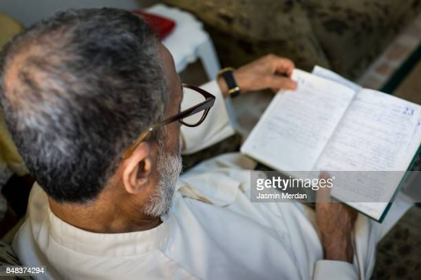 Old man with grey beard checking notes