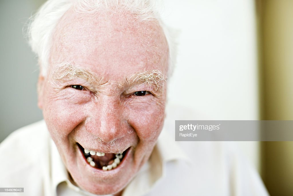 Old man with missing teeth smiles happily : Stock Photo