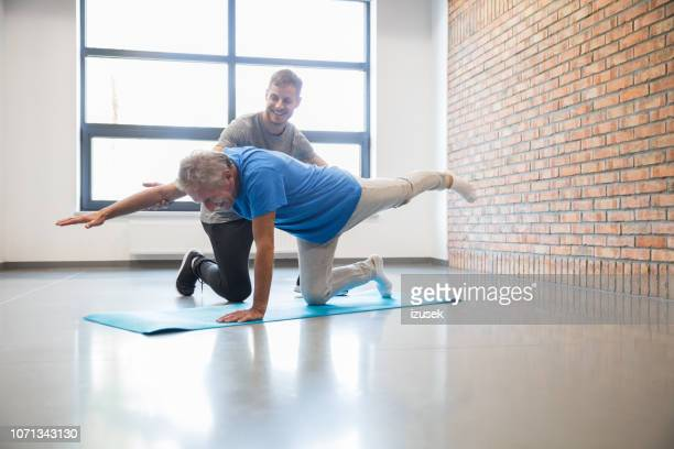 old man with personal coach exercising at rehab centre - drug rehab stock pictures, royalty-free photos & images