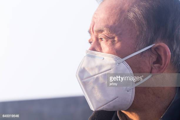 old man with respirator in the mist