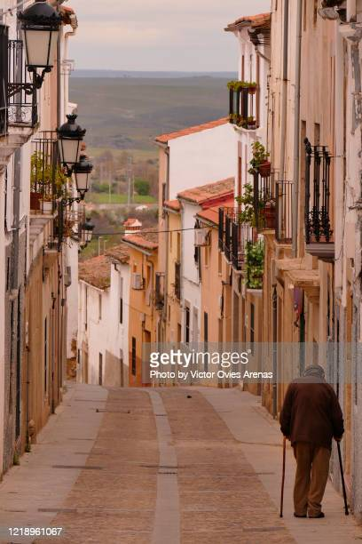 old man with two sticks walking down an old street in caceres with the countryside and the horizon in the background - victor ovies fotografías e imágenes de stock