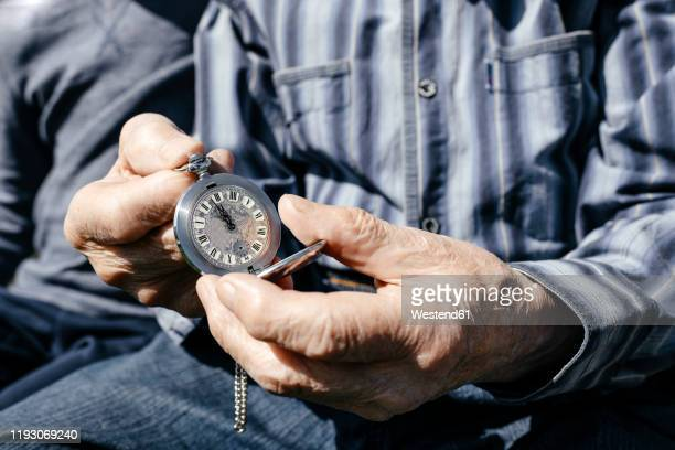 old man's hands holding silver pocket clock, close-up - souvenir stock pictures, royalty-free photos & images