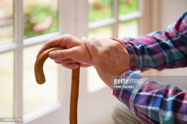 old man's hands on walking stick in care home - body care stock pictures, royalty-free photos & images