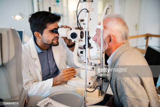 old men having an eye exam at ophthalmologist's office. - optical instrument stock pictures, royalty-free photos & images