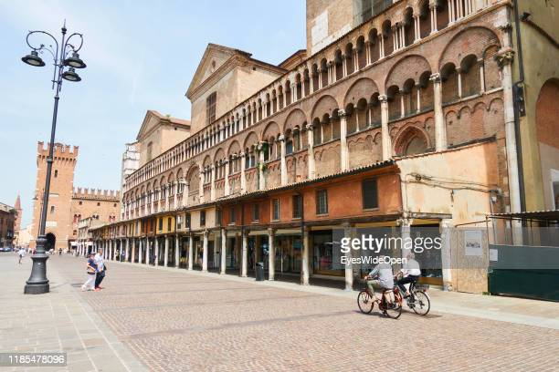Old men on a bicycle and tourists in the historic center at Piazza Cattedrale on June 8, 2019 in Ferrara, Italy.