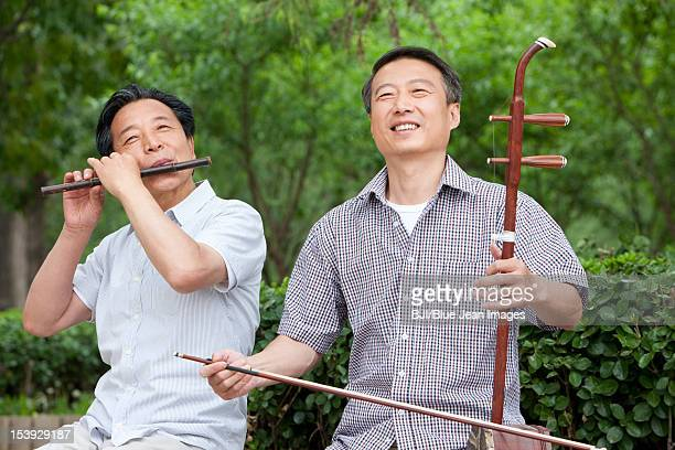 old men playing chinese traditional instrument in park - traditional musician stock photos and pictures