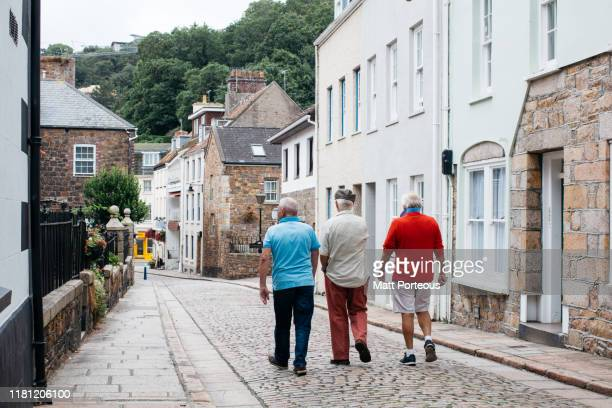 old men walk down cobbled streets - british people stock pictures, royalty-free photos & images