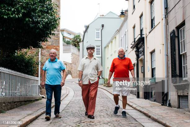 old men walk down cobbled streets - town stock pictures, royalty-free photos & images