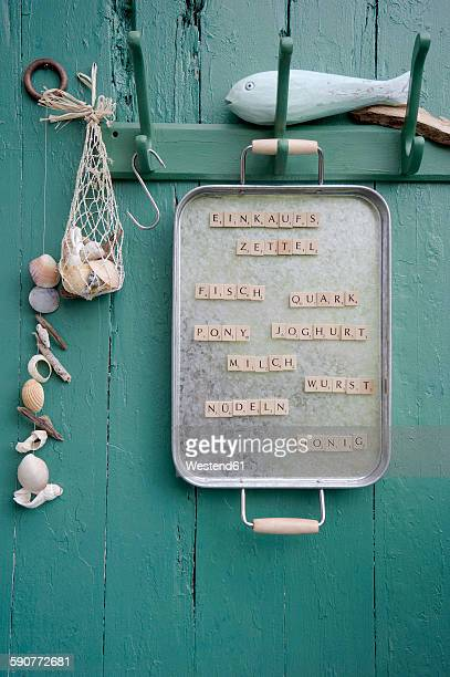 Old metal tray with magnetic scrabble tiles used as shopping list hanging on coat rack