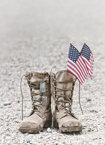 Old military combat boots with dog tags and the American flags 973664770