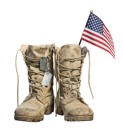 Old military combat boots with the American flag and dog tags 1062334648
