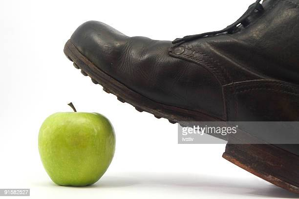 Old military shoes and green apple
