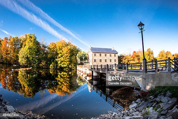 """old mill and autumn trees reflected in still river - """"danielle donders"""" stock pictures, royalty-free photos & images"""