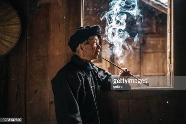 alten Minderheit chinesischer Mann Pfeife am Fenster