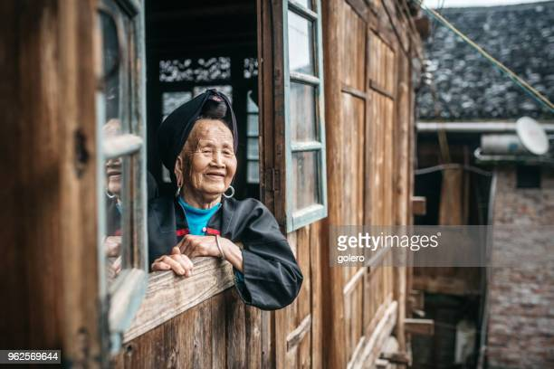 old minority chinese woman looking out of window - east asia stock pictures, royalty-free photos & images
