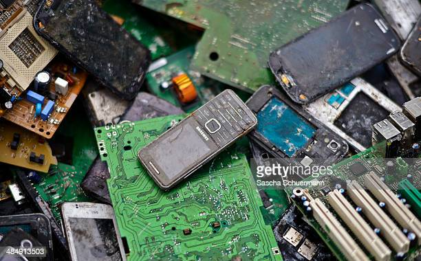 Old mobile phones lie between electronic components including circuit boards sit in a pile ahead of recycling at Aurubis AG metal refinery on...
